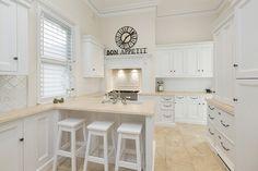 cuisine-blanche-sol-plans-travail-pierre-beige-horloge-vintage