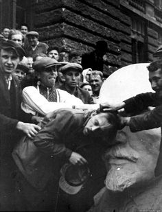 A Jewish man in western Ukraine being attacked by a mob next to a bust of Lenin, 1941