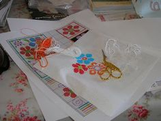 crafting magazines I design for give their readers a big package of gorgeous craft materials with each issue. The designers work with the same kit, creating projects to inspire creativity. The picture shows a cross stitched flower project in the middle of being stitched The flowers were made into cards with ribbons, beads, sparkly sequins and paper embellishments .