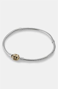 A logo-etched, 14-karat gold clasp gives two-tone versatility to a silver charm bracelet boasting a threaded design that secures a collection of charms. Color(s): silver/ gold. Brand:... More Details