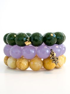 A stack of three striking 14mm faceted stone Mardi Gras bracelets.   Perfect for a parade, ball, or crew party. Elastic cord.
