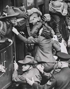 On a crowded railway platform, two soldiers hoist a woman on their shoulders so she can kiss her sweetheart goodbye. Second World War. August 14, 1940.