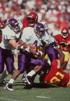 Running back Corey Dillon of the Washington Huskies keeps his eyes focused up field as he runs through a hole in the line of scrimmage while being...
