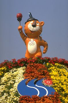 Hodori, the Olympic mascot, holds the Olympic torch above his head while standing on top of a mountain of flowers during the 1988 Seoul Olympics. (Photo by David Cannon/Getty Images)