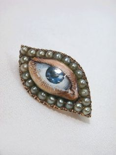 Eye miniature Circa 1800  An enigmatic enamel eye in the overall eye shape referred to as a shuttle shape, used only for a few years around 1790-1800 or a touch later.  The enameled eye is surrounded by a row of pearls. It measures 1 1/16  inches long by 9/16 inches high, so is quite petite. It is set into rose gold. The eye is blue, with tiny lashes and detail down to the corner of the eye, and lifelike skin and all.