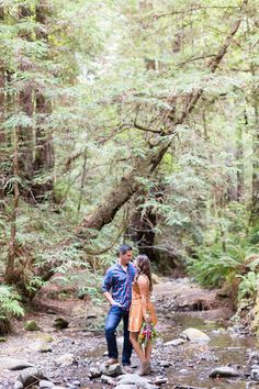 Engagement Portrait Standing in Creek Looking at Each Other Holding Flowers   Half-Moon-Bay-Redwood-Engagement-Wedding-Photographer-TréCreative