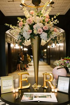 Gold initials and a tall floral arrangement decorated the welcome table.   	Venue: Oxford Exchange  	Wedding Planning: Michelle Bastone of One Fine Day, Inc.  	Floral Design: Botanica International Design Studio