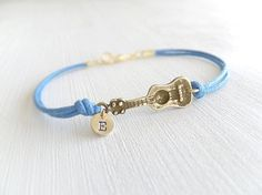 This is a cute ukulele guitar bracelet, attached of a little coin with personalized letter. Its a double tie in ocean blue cotton cord. Charm