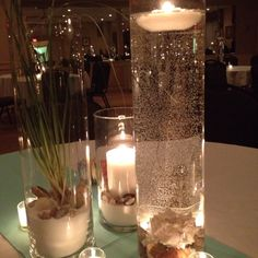 Beach themed centerpiece using white sand, sea oats, sea shells, water, and lots of candles.