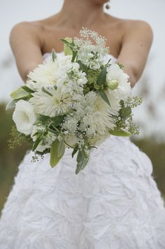 The bridal bouquet will be a naturally-shaped, rustic bouquet of white and green Queen Anne's lace, green lamb's ear, ivory garden roses, ivory stock flowers, chocolate cosmos, and white scabiosa flowers wrapped in ivory linen with the stems showing.