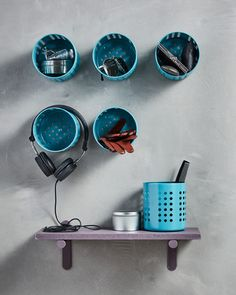 Six IKEA ORDNING utensil holders have been spray painted blue and are screwed to the wall to function as storage.