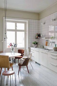 Biała podłoga, białe meble, białe kafle na ścianie – monochromatyczna baza tej kuchni jest neutralnym tłem dla oryginalnej kompilacji krzeseł. Różnorodność ich form i obić porządkuje spójna gama kolorystyczna. Tapicerowane siedziska sprawiły, że kącik jadalniany nabrał niezwykłej wygody i przytulności.