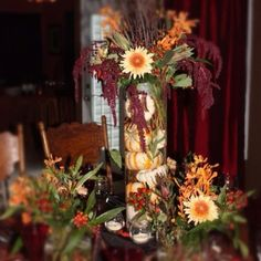 Mini pumpkins fill this vase to balance the heavy florals.