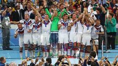 Philipp Lahm of Germany lifts the World Cup trophy with teammates