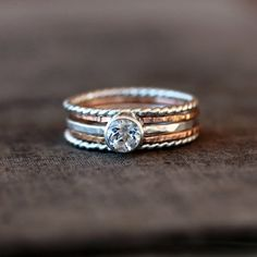 This mix of 14k gold and sterling silver rings stacks together for an awesome statement effect on the finger. The centerpiece is a Topaz gemstone