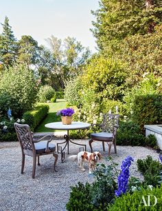 A terrace featuring teak armchairs from Treillage with Perennials-fabric seats | archdigest.com