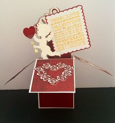 This handmade card is perfect for Valentines Day. As the recipient removes the flat card from the envelope they will be delighted as the card transforms into a delightful box containing a rose wreath, love sign, double hearts, and xoxo pop ups. The front panel displays Happy