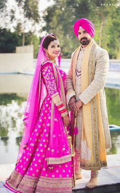 Sikh Wedding Bride - Couple Shot with the Bride in a Rani Pink Anarkali Suit with Golden Embroidery and the Groom in a Gold Sherwani with a Peach Safa and Pink Pug | WedMeGood #wedmegood #indianbride #indianwedding #pink #sherwani #anarkali #coupleshot