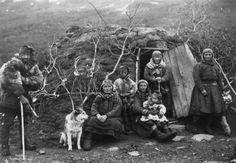 Svenske samer og en hund utenfor døråpningen til en gamme, fem voksne og to barn. Nord-Norge 1906.