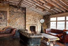 brick wall, rustic ceiling, worn leather couches, wood floors