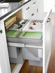 Concealed Trash Bins Compact trash center gets the job done. A false-front door/drawer conceals four compartments that easily slide out from under the counter.
