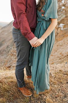 Fall Engagement Session - Red Lodge - Montana - Beartooth Pass - Beartooth Highway - Man - Woman - Engaged - Couple - Fiancé - Outdoor - Overlook - Mountains - Rocks - Maroon Dress Shirt - Burgundy Dress Shirt - Gray Pants - Gray Jeans - Blue Dress - Teal Dress - Wedding Ring - Diamond Ring - Ring Shot - Holding Hands - Neck Down - Montana Wedding Photographer - Sara Nagel Photography Fall Engagement, Engagement Couple, Engagement Session, Engagement Photos, Gray Jeans, Grey Pants, Maroon Dress Shirt, Shirt Dress, Dress Wedding
