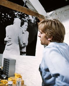 David Hemmings examines an image of a couple embracing in a scene from the film 'Blowup' Great Britain 1966, the thriller directed by Michelangelo Antonioni (Getty Images)