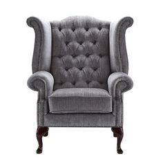 Make a style statement with this eye-catching armchair, showcasing a traditional wing-back design with opulent scrolling arms, a button-tufted back and nailhead detailing.