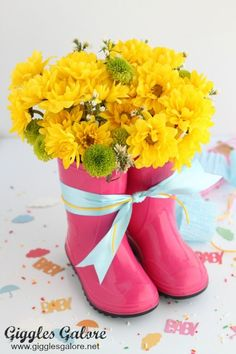 """April showers bring baby showers and an adorable Rain Boot Flower Arrangement. This adorable flower arrangement is perfect for a spring themed party or April Showers themed baby shower. I am planning a baby shower with the theme """"April Showers"""" and I found some of the cutest party supplies to create an extraordinary party for …"""