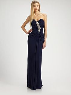 """Badgley Mischka  Strapless Jersey Gown  Be The First to Write a Review  Impeccably draped jersey, embellished with allover ruching and a glamorous beaded detail.        * Strapless sweetheart neckline      * Jeweled, ruched bodice      * Front drape      * Concealed back zip      * Fully lined      * About 44"""" from natural waist      * polyester/rayon      * Spot clean      * Imported"""
