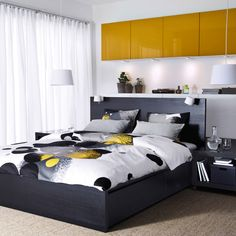 A bedroom with a black brown MALM bed, BESTÅ storage with yellow doors and BOLLTISTEL quilt cover