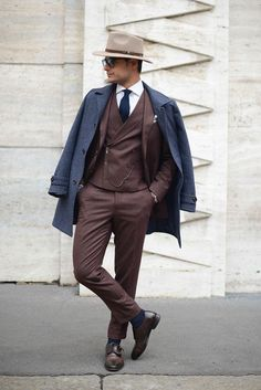 Shop this look on Lookastic:  http://lookastic.com/men/looks/hat-dress-shirt-tie-double-monks-socks-three-piece-suit-overcoat/8825  — Tan Wool Hat  — White Dress Shirt  — Navy Tie  — Dark Brown Leather Double Monks  — Navy Socks  — Dark Brown Three Piece Suit  — Navy Overcoat