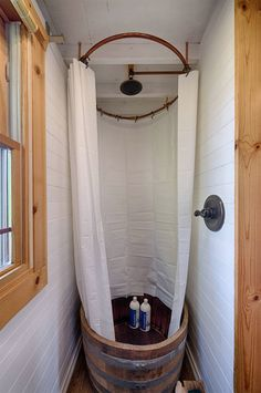 The bathroom in this tiny house is fitted with a wine barrel shower.