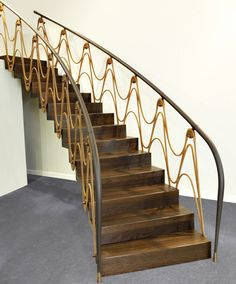 ST890 Curved zigzag stair made of smoked oak. Balustrade of Corten steel and brass, handrail with leather cladding. Designed by TRĄBCZYŃSKI.