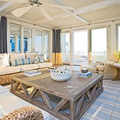 an oversize coffee table anchors the space and suits its large size; architectural detailing like coffers and a tongue-and-groove ceiling warm up the voluminous room. Framing the glass doors are colorblock draperies; the blue signifies