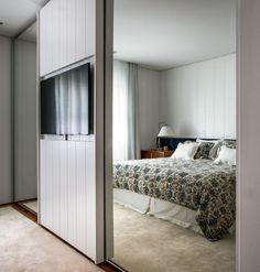 Quarto de casal   Ladeada por enormes espelhos que revestem as portas do armário, a TV fica embutida em uma peça de marcenaria. Projeto Ouriço Arquitetura (Foto: Foto: André Nazareth/Divulgação)