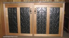 Pressed tin gives a classy effect to cupboard doors. this is the Vines (D) design. To learn more about this design please see: http://www.heritageceilings.com.au/tempat/vines.php