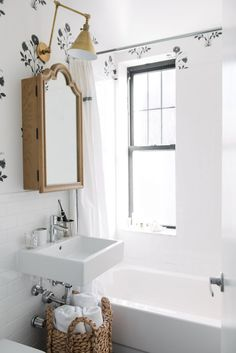 small bathroom with gold fixtures and wallpaper