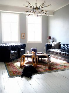 love the simplicity of the slightly grey walls, black leather furniture, and a muted yet colorful rug. it's open and lovely, yet simple.
