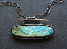 """made with a beautiful drusy chrysocolla stone and an intesting sterling silver double bezel. oxidized silver to compliment the earthiness of the stone and bring out the depth of the double bezel. Pendant measures 1 5/8"""" across x 7/8' tall. Chain measures 17"""" and finishes with a toggle clasp in the front."""
