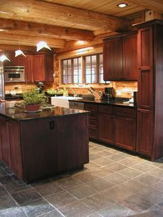 Cedar log home, Kitchen area. Slate floors, large cedar log walls and beams.   http://www.huismanconcepts.com/