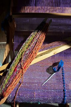 Weaving in the Saori style on a rigid heddle. I like the thicker bits of fiber added with a needle. Creative.