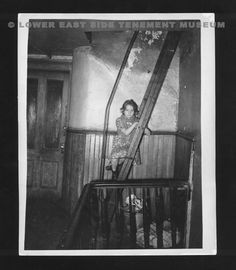 "A young girl sits on a ladder in the hallway of a Lower East Side tenement. Photograph was a part of the ""One Third of a Nation: The WPA Photographs of Arnold Eagle"" November 1988 exhibit at the Lower East Side Tenement Museum, 97 Orchard Street. (New York, 1935)"