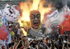Protesters burn an effigy of Philippine President Benigno Aquino III during a rally to coincide with his fourth State-of-the-Nation Address (SONA) before the country's congressmen and senators Monday July 22, 2013. President Aquino III is expected to dwell on the gains of his administration particularly on the robust economy but the protesters see otherwise especially on the increasing prices of oil and basic services as water and electricity. (AP Photo/Bullit Marquez)