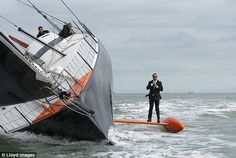 Eat your heart out Bond: Performing a stunt known as 'The Keel Walk', British skipper Alex Thomson adjusts his tie aboard his Hugo Boss racing yacht