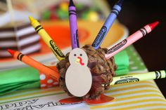Kids Thanksgiving Table Ideas:  Bright crayons create a colorful turkey feathers. Print up some Thanksgiving themed pages and keep kids busy while they wait for dinner.