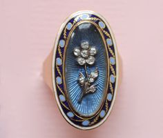An exquisite gold oval ring with behind glass a cartouche with a guilloche and transparant light blue enamel decorated with a forget-me-not flower in old cut diamonds set in silver, around this a border of gold, light blue and dark blue enamel and a second border of white enamel, 18th century.  weight: 6.3 grams ring size: 17 mm. 6 ¾ US. www.inezstodel.com