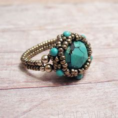 A rose cut turquoise is intricately set in a woven bronze glass bezel. Turquoise beads and sterling silver accent the setting throughout. The band is somewhat flexible, and the ring is lightweight and