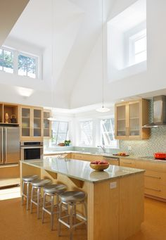 Kitchen with stainless steel appliances and light wood cabinets. Kitchen island with metal stools
