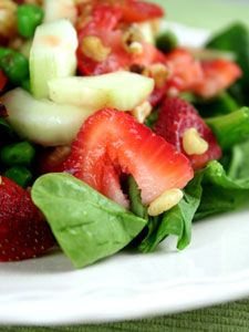 Strawberries and cucumbers with a honey vinaigrette and served on spinach greens.